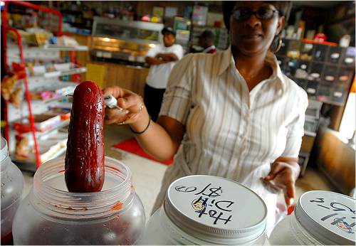 Beverly Boddie pulling a red kool-aid pickle out of a jar in cleveland, mississippi