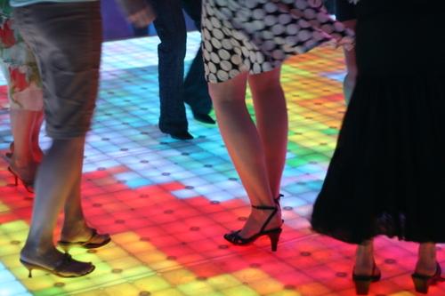 people dancing on a multi-colored dance floor
