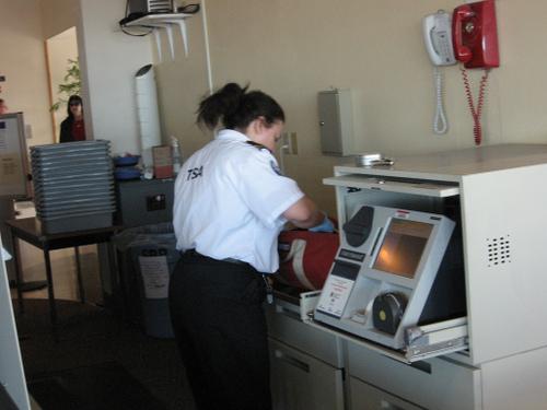 TSA agent checking my bag by Joel Franus
